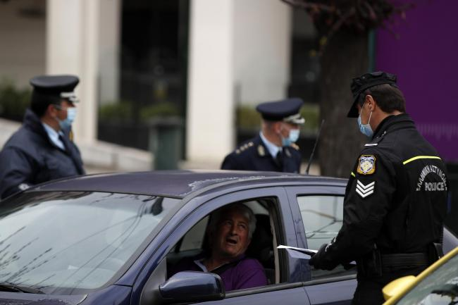 A traffic police officer checks a driver for valid documents in Athens