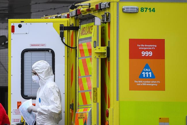 A paramedic wearing personal protective equipment (PPE) exits an ambulance outside St Thomas' Hospital in Westminster, London, as the UK continues in lockdown to help curb the spread of the coronavirus. PA Photo. Picture date: Monday March 30, 2020. A