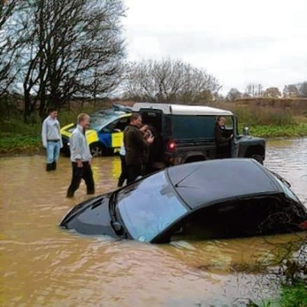 Students from Writtle College try to recover a car caught in the floods