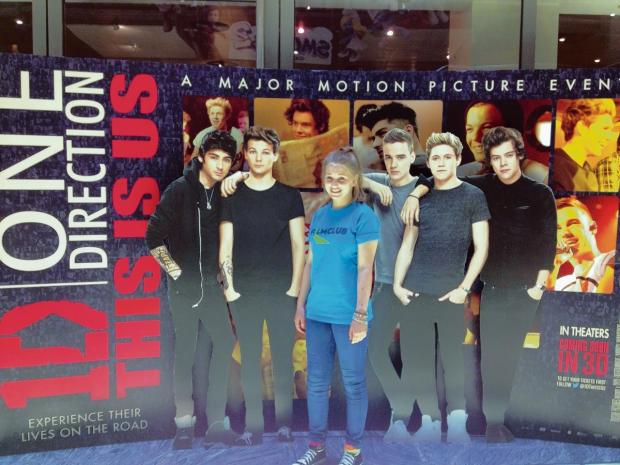 Laura McAuley with cardboard cut-out images of One Direction