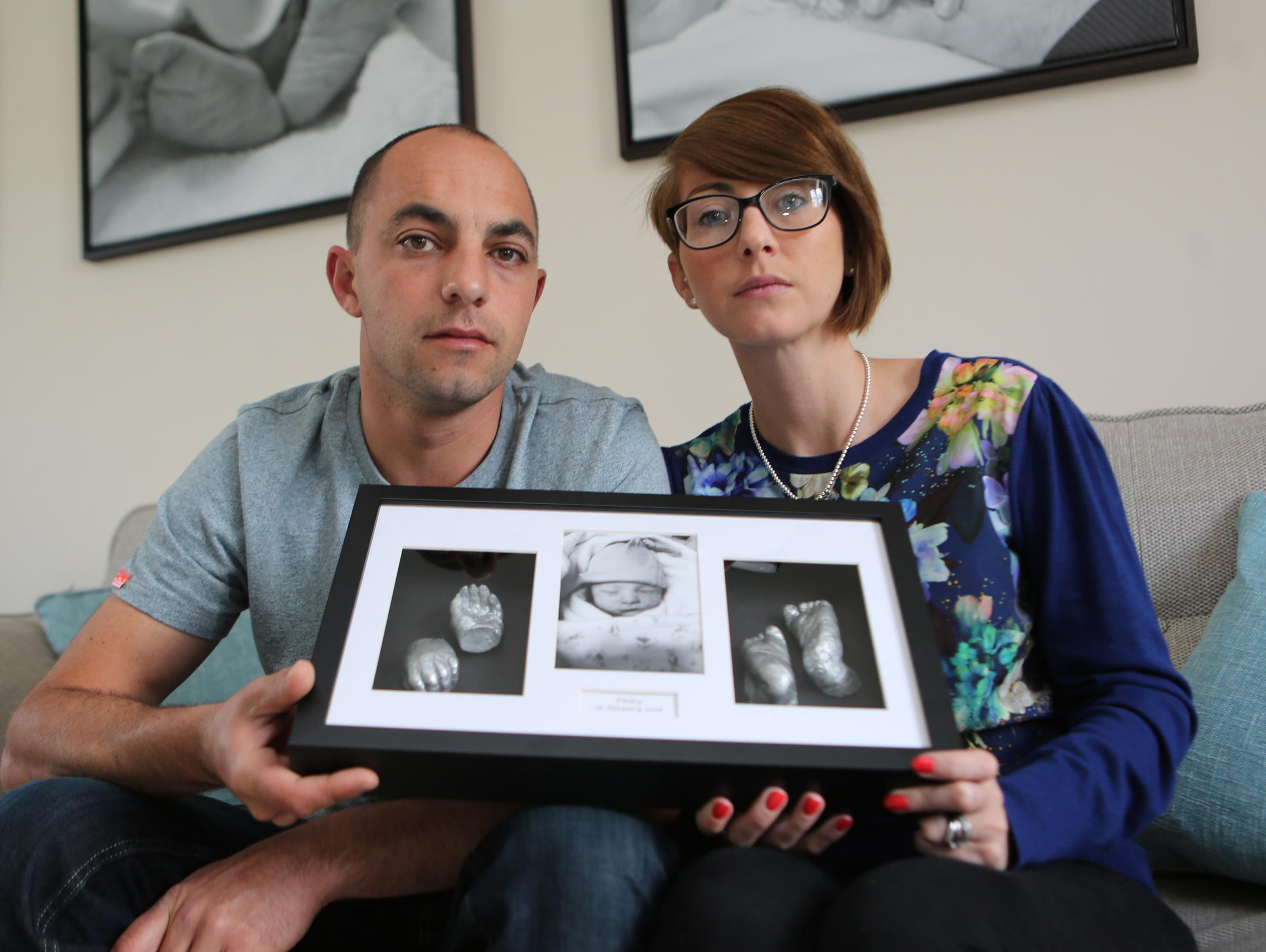 Robert and Charlotte Smith with framed castings of their son Finley's hands and feet.